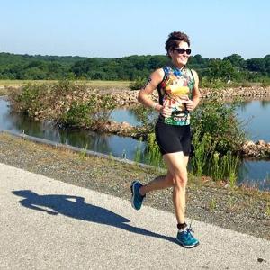 photo of Mary Braun cruising around the reservoir in the 2015 Top of Delaware Sprint Triathlon